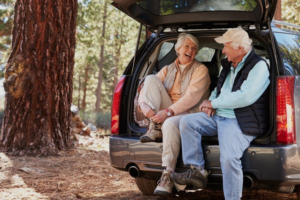 Older Couple in SUV in woods
