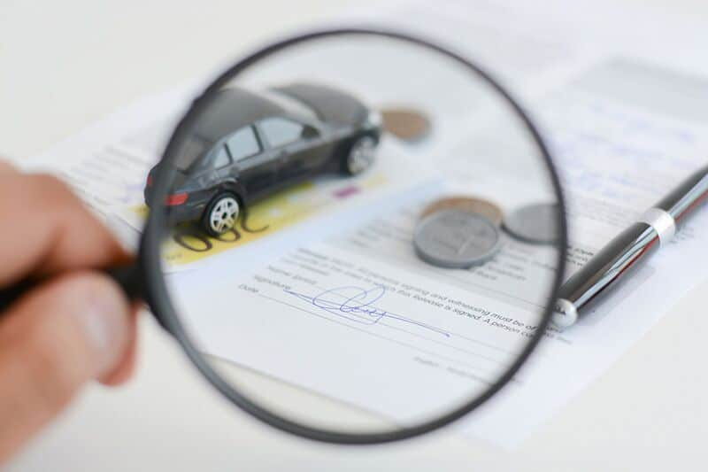 car insurance policy being looked at with a magnifying glass, car insurance myths