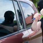burglar about to smash car window, the relationship between crime rate and your auto insurance